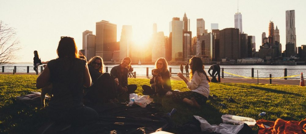 Group of friends having a picnic in a park with New York City skyline behind them