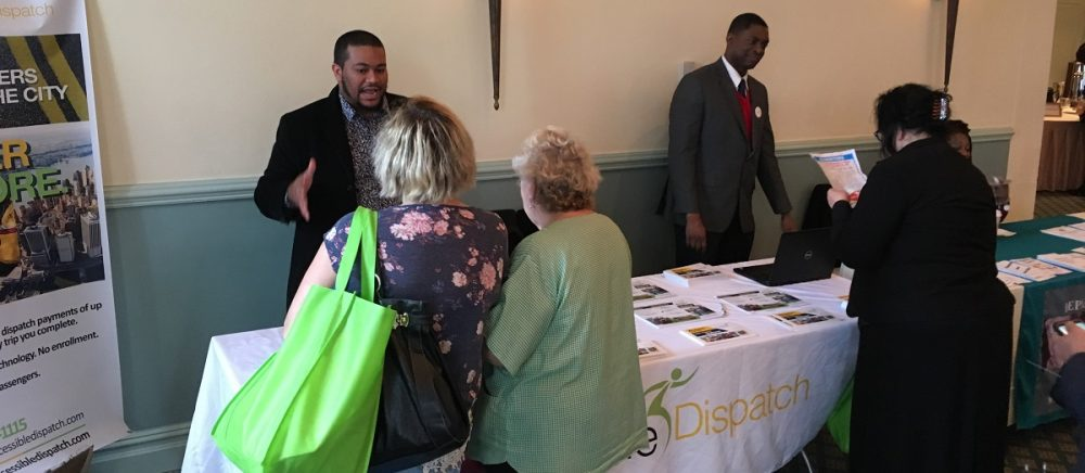 Photo of two members of the Accessible Dispatch outreach team speaking with individuals about the Accessible Dispatch program at a recent event.