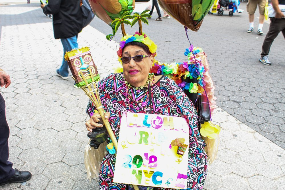 Woman in a wheelchair holds a sign and balloons while she celebrates at the Disability Pride Parade 2018 in colorful, festive attire.