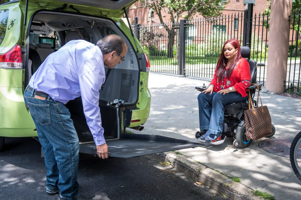 A woman in a wheelchair waits on the curb of a New York City street as her driver deploys the ramp of his wheelchair accessible vehicle.
