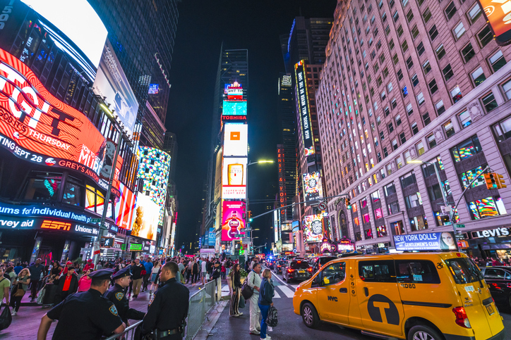 A photo shows a crowded Times Square at night time. A yellow wheelchair accessible taxi is shown in the foreground.