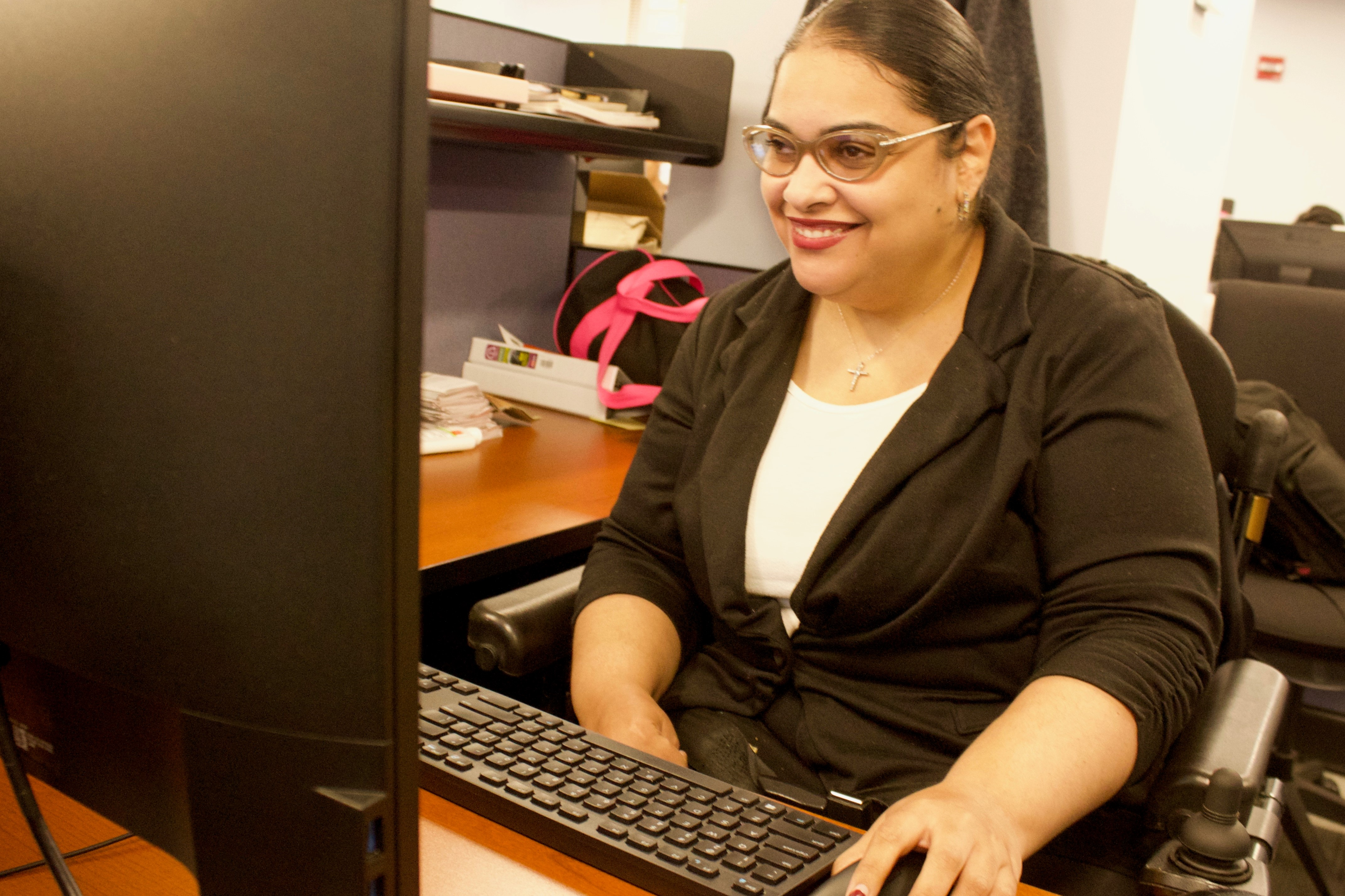 Crystal Rivera, Program Officer for Special Projects, Office of Financial Empowerment/EmpoweredNYC, working diligently on a computer at her desk.