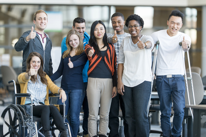 Diverse group of college students smiling and showing a thumbs up. One of them is in wheelchair and one is with crutches.