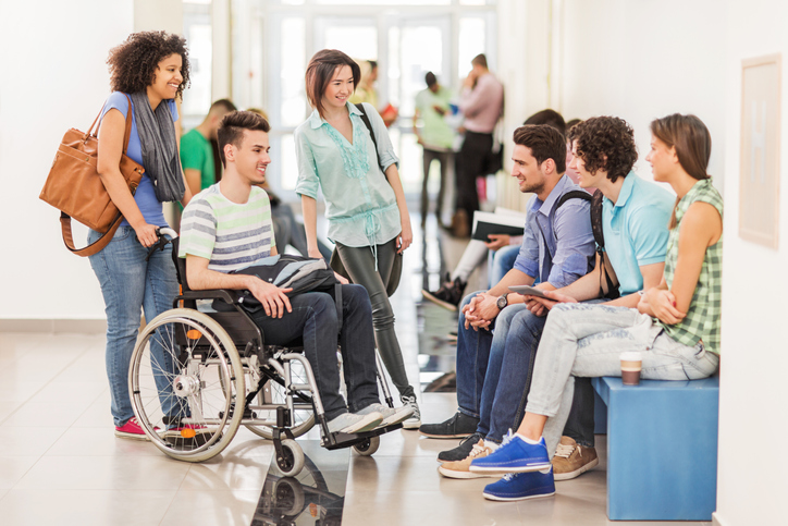 Group of students having a break and talking to each other in the corridor. One of them is in a wheelchair.