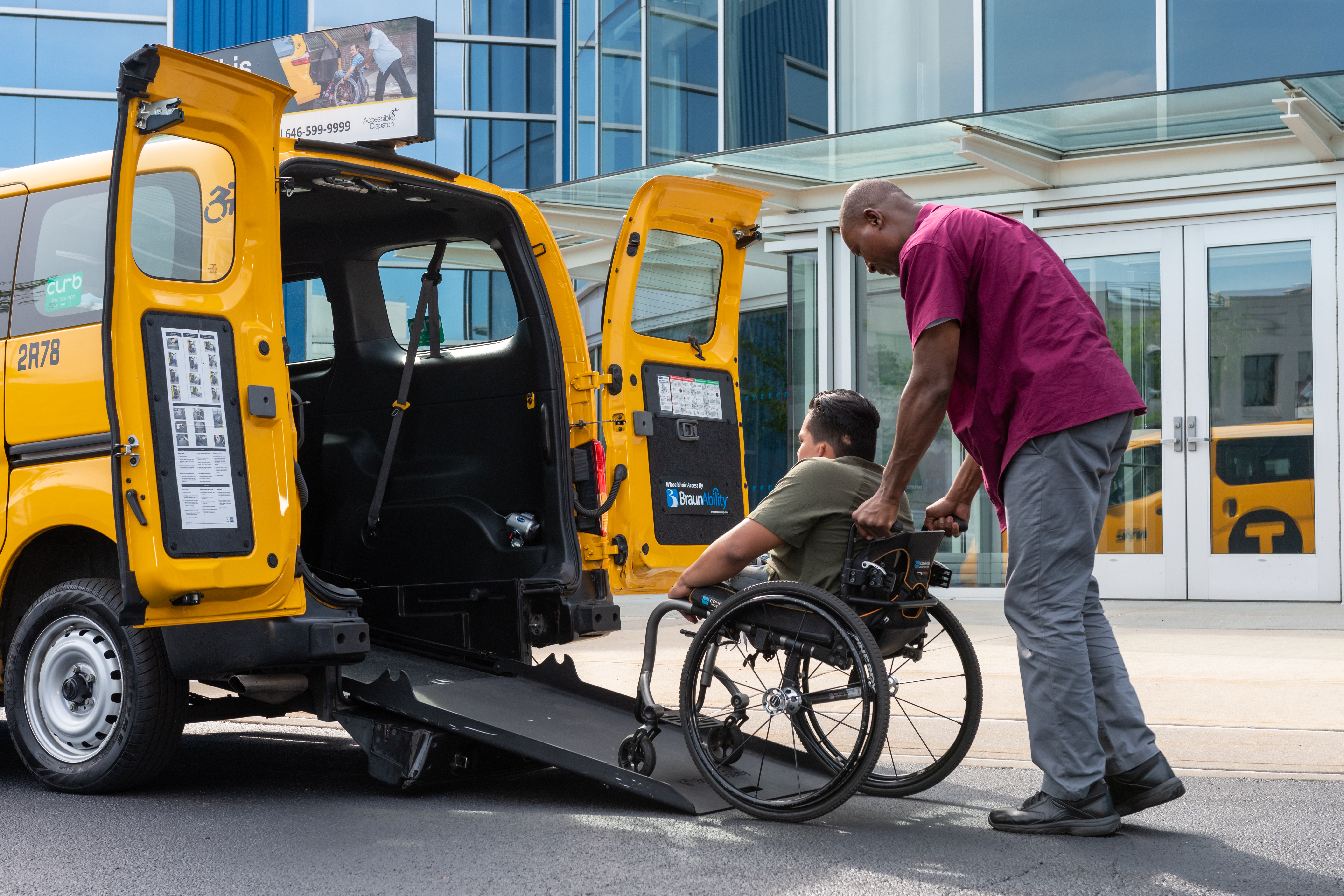 A TLC-Licensed yellow cab driver helping a passenger with wheelchair board a Nissan NV200.