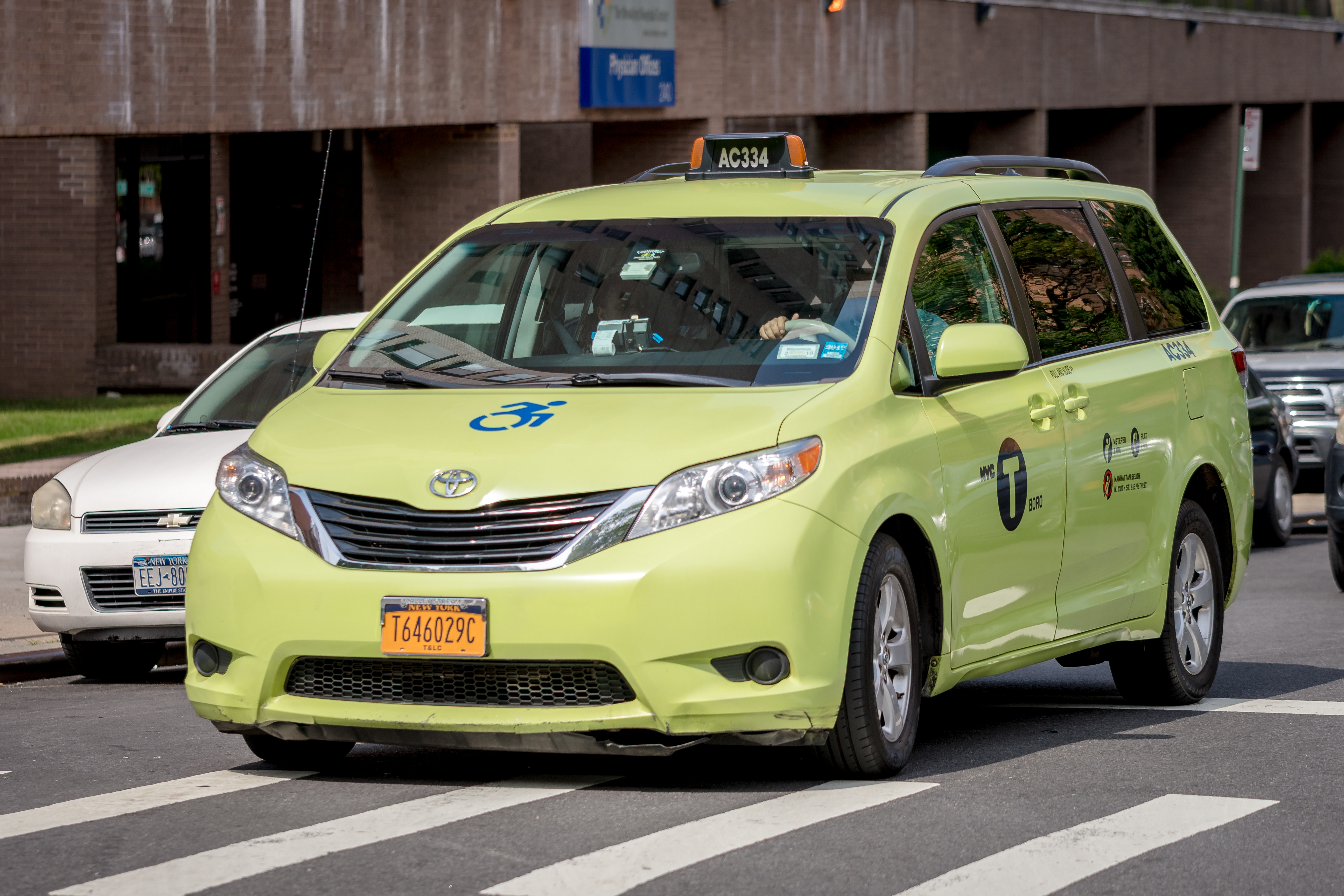 A green wheelchair accessible Toyota Sienna travels down a New York City street.