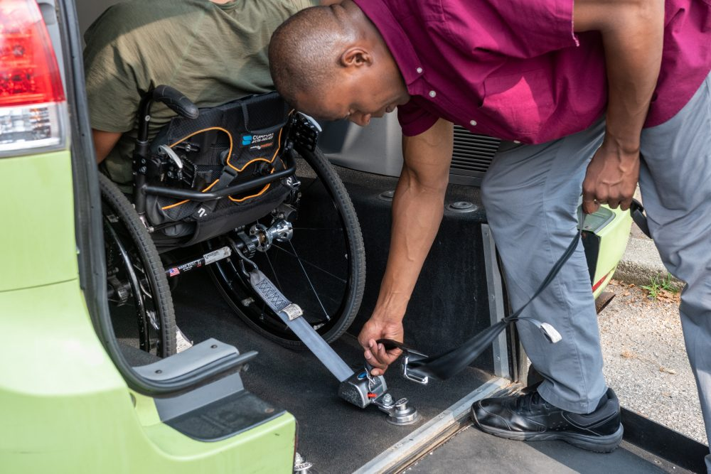A driver secures his passenger's wheelchair in the rear of his green wheelchair accessible taxi using the securement straps.
