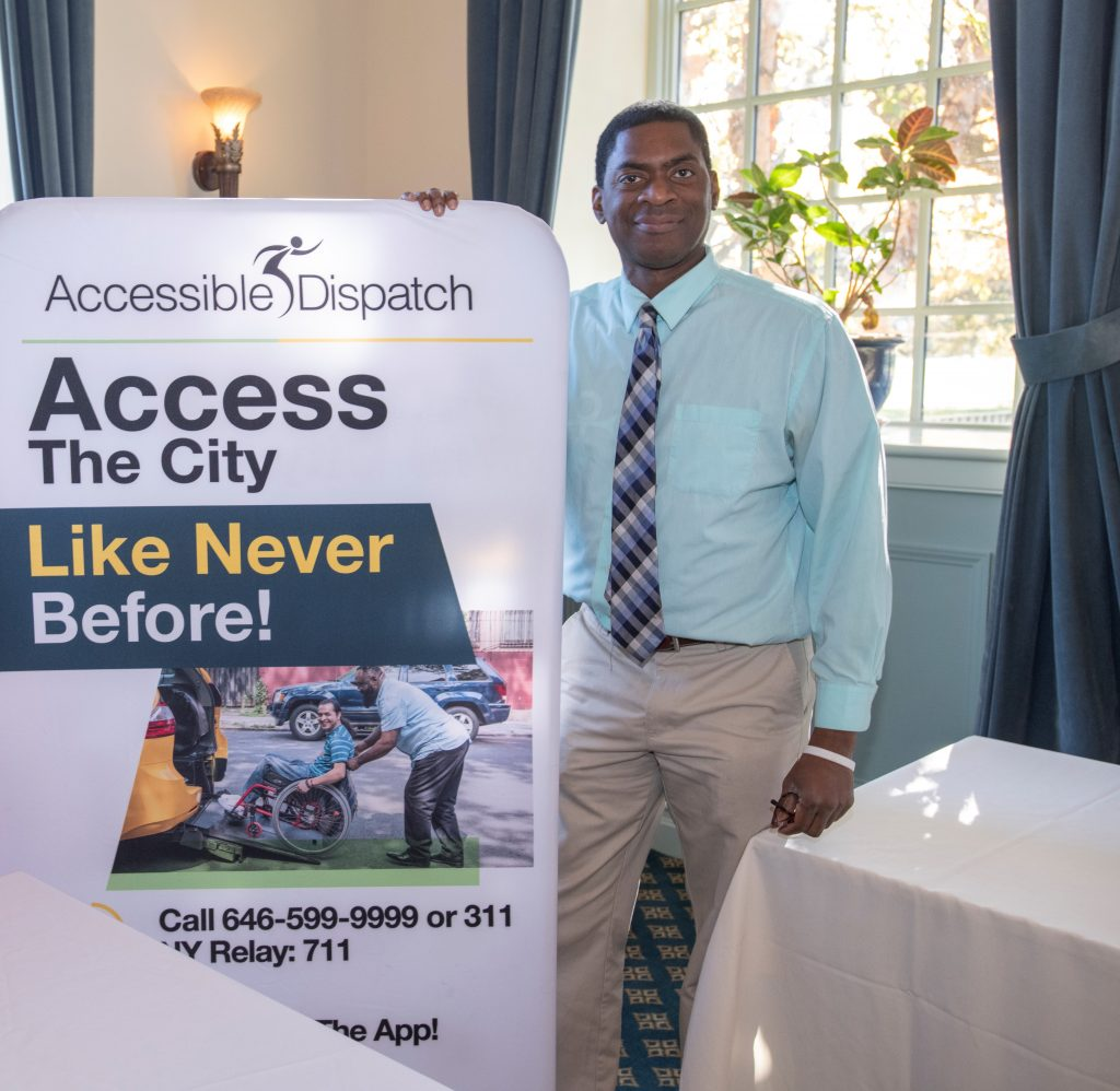 """Accessible Dispatch Community Outreach Trainer Steven Williams stands beside a sign promoting the Accessible Dispatch program. The sign reads """"Access the City Like Never Before."""""""