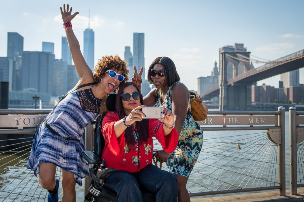 Photo of a woman in wheelchair with two friends posing happily in front of the New York City Skyline.