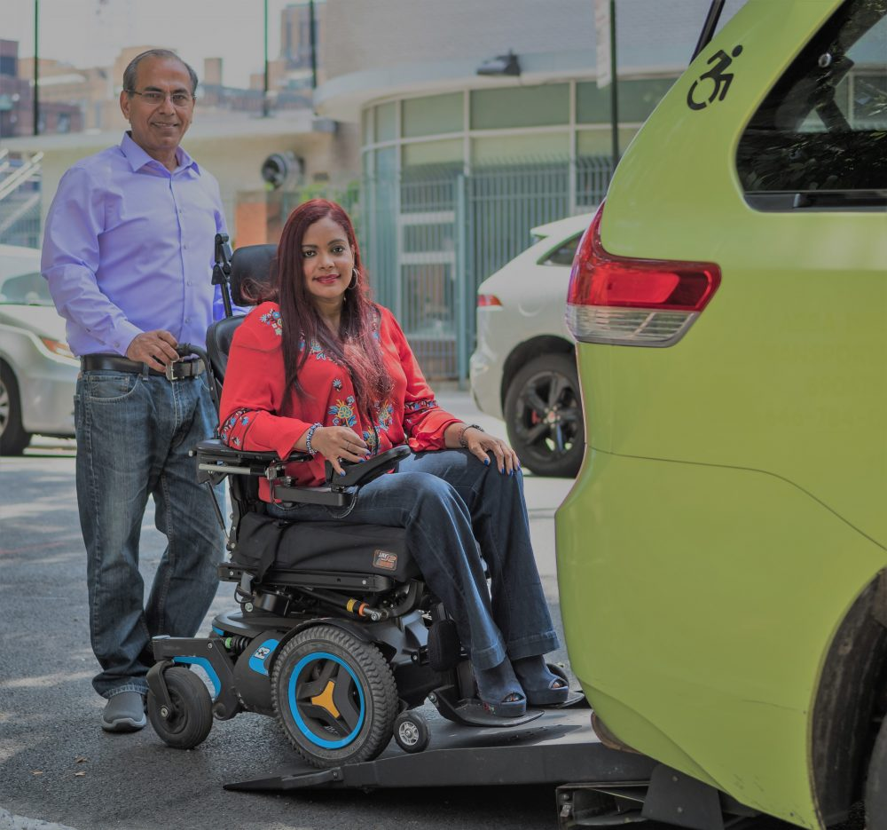 Green wheelchair accessible taxi driver with a happy customer, standing next to the cab and smiling