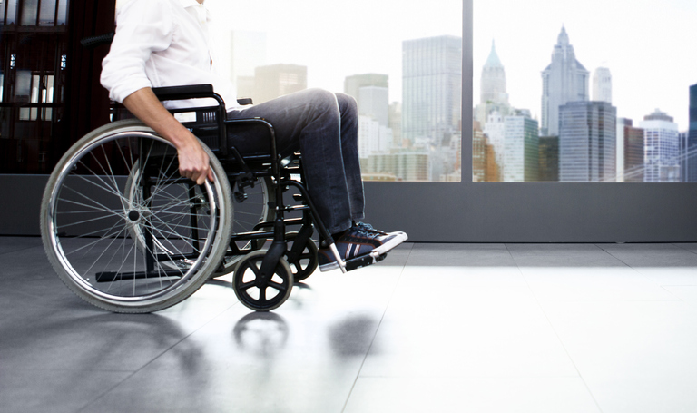 Young man in a wheelchair sits in front of a window with New York City highrises in the background.