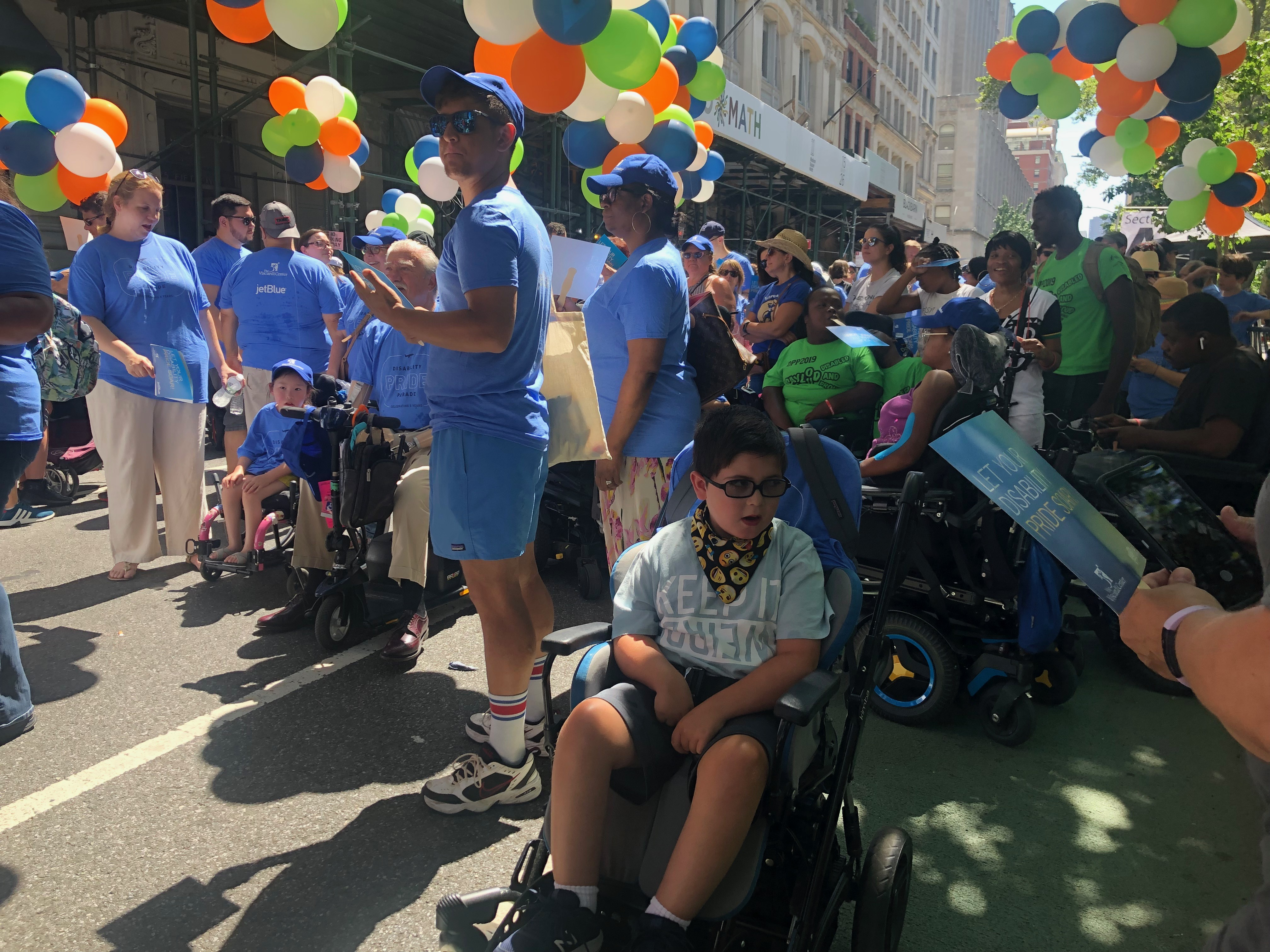 A young boy in mobility device getting ready to march in fifth annual disability pride parade, New York.