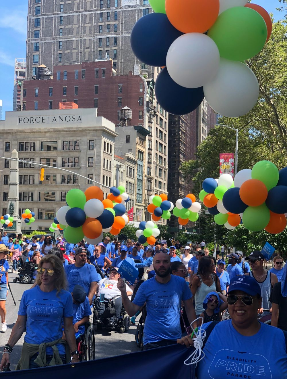 Enthusiastic volunteers marching in Fifth Annual Disability Pride Parade.