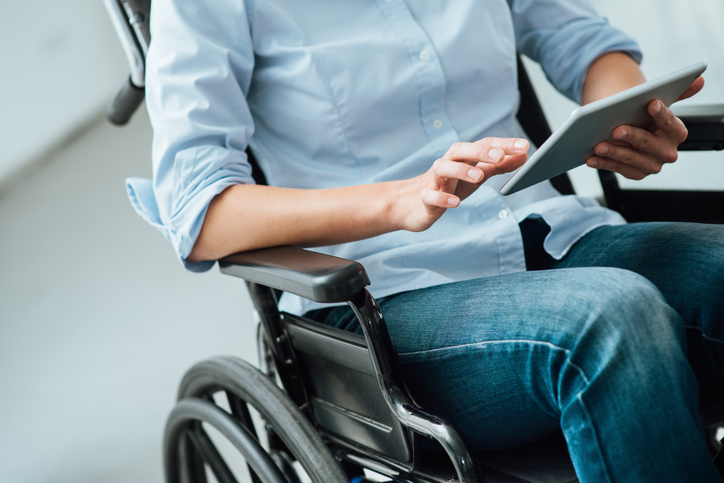 • Close up image of a woman in wheelchair using a digital touch screen tablet.