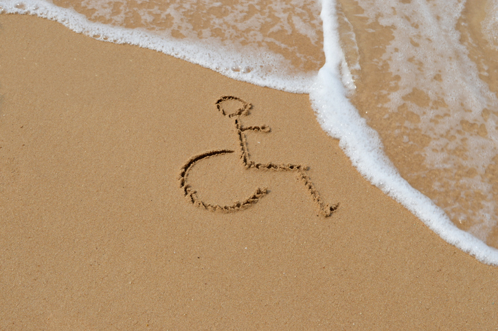 Wheelchair accessible sign carved into the sand on a beach with waves approaching.