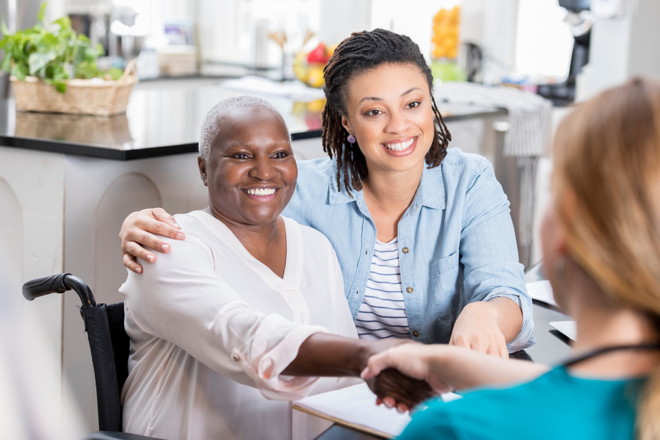 A woman talks with her mom's home healthcare nurse. The daughter has her arm around her mom. The mother is shaking the nurse's hand.
