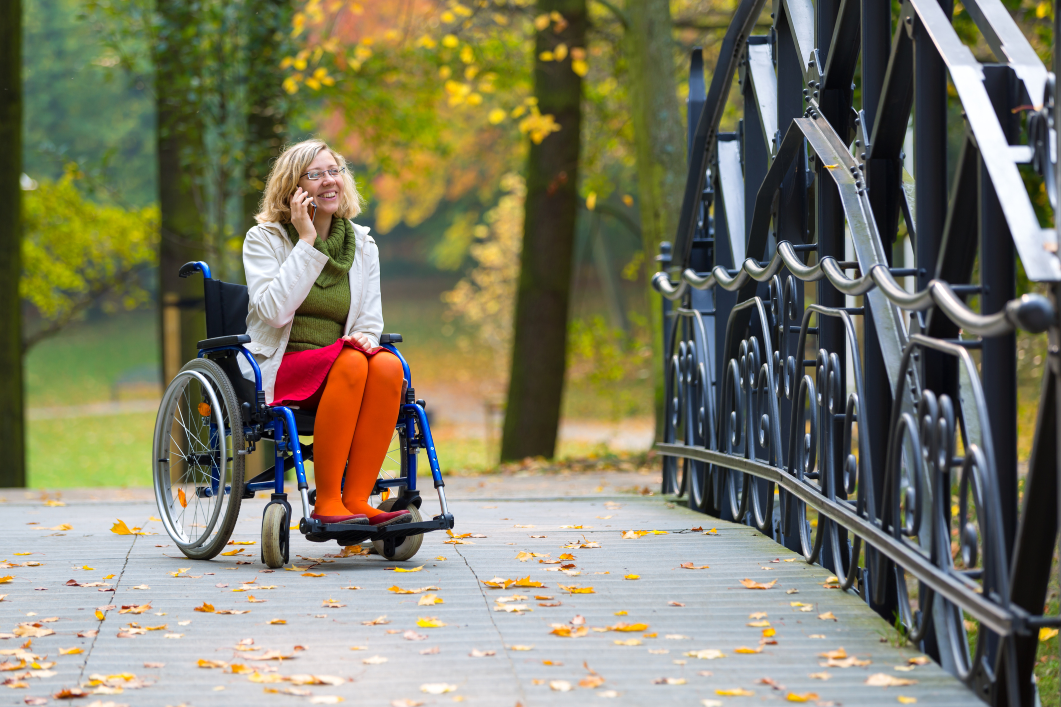 Happy woman on wheelchair talking on the phone in the park in autumn.