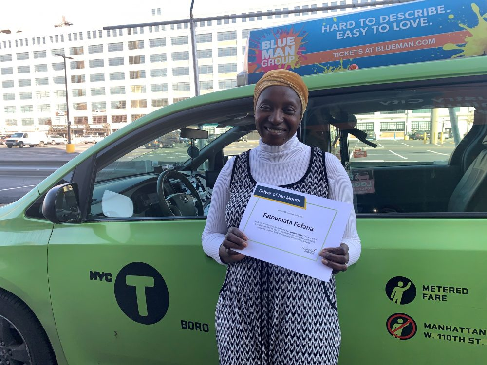 Fatoumata Fofana holds her certificate for October 2019 Driver of the Month while standing in front of her green wheelchair accessible taxi.